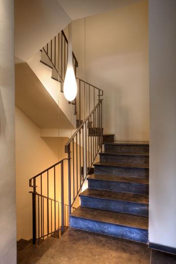 חדר המדרגות המוביל לדירה. אבן צפחה, מעקה שנראה פשוט ומנורות בצורת טיפה (צילום: אסף פינצ'וק)