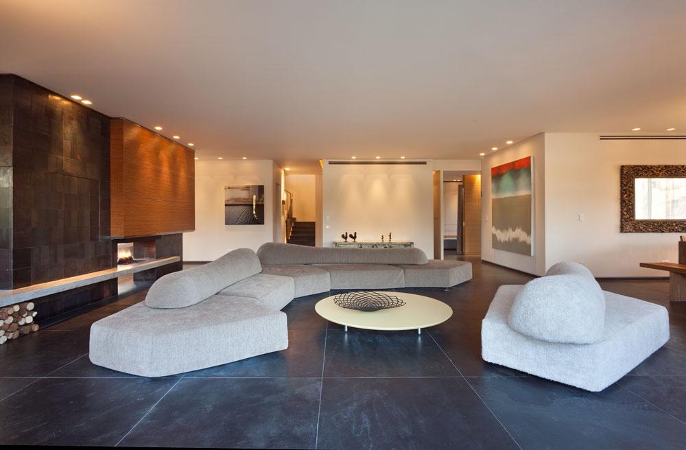 את האיפוק המינימליסטי ''מחממים'' חומרים שחוזרים בעיצוב הפנים של הדירה: אבן צפחה שחורה על הרצפה, עץ אלון טבעי ופלדה על קיר האח. מסך הטלוויזיה שלצד האח מסתובב לשני הכיוונים (צילום: אסף פינצ'וק)