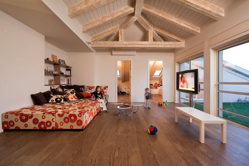 ''סלון'' הילדים, עם ספה גדולה שהוזמנה אצל רפד ומספקת לילדים כר נוח לרביצה ולקפיצה, ויציאה למרפסת גדולה, מחופה דשא סינטטי (צילום: אסף פינצ'וק)