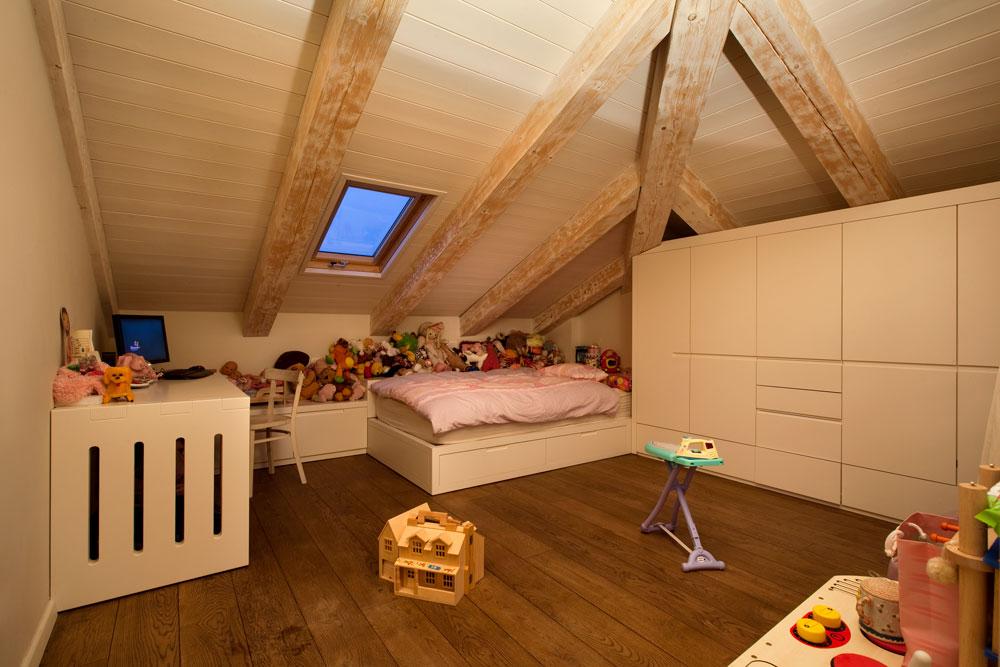 אחד מחדרי הילדים בקומה העליונה, שחופתה עץ אלון טבעי ותקרתה משופעת וצבועה לבן משויף, במראה כפרי חם (צילום: אסף פינצ'וק)