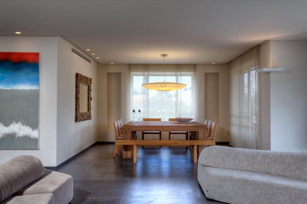 שולחן האוכל מרובע, בגודל של 180 על 180 ס''מ, וסביבו מקום ל-12 סועדים. מעל תלויה מנורה של המעצבת איילה צרפתי. מימין המרפסת ומשמאל הקיר המשותף עם חדר השינה (צילום: אסף פינצ'וק)