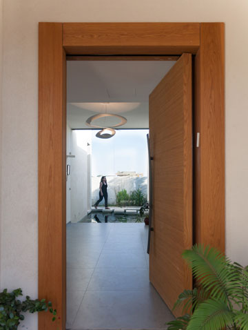 דלת הכניסה הגבוהה נפתחת למבואה, שמולה נבנתה בריכה ביולוגית וביניהן מפריד קיר זכוכית שקוף (צילום: לוסיאנו סנטנדראו)