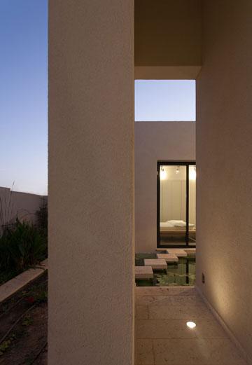 המעבר מחדר השינה, דרך הבריכה הביולוגית, לגינה שפונה אל הנוף (צילום: לוסיאנו סנטנדראו)