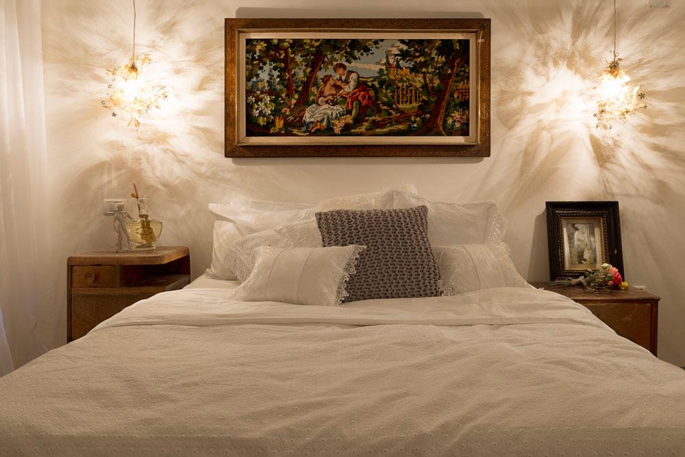 מיטת עץ בין שתי שידות שאינן תואמות, ותמונת גובלן בין שתי מנורות בעיצוב טורד בונטייה, שנקנו בחו''ל ב-20 דולר לאחת (צילום: גדעון לוין 181 מעלות)