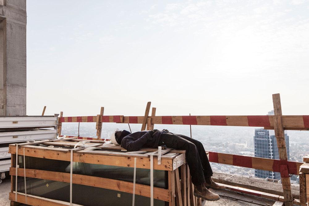 רגע של מנוחה באתר הבנייה, שפועל יומם ולילה כמעט ללא הפסקה, במאמץ להספיק ולאכלס את הבניין עד סוף השנה (צילום: אביעד בר נס )