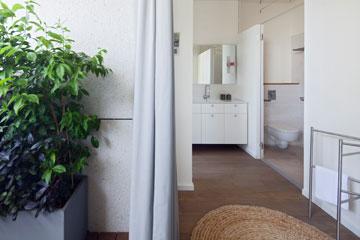 כיור הרחצה פתוח לחלל חדר השינה. דלתות זכוכית מפרידות בינו לבין השירותים והמקלחון (צילום: עמית גרון)