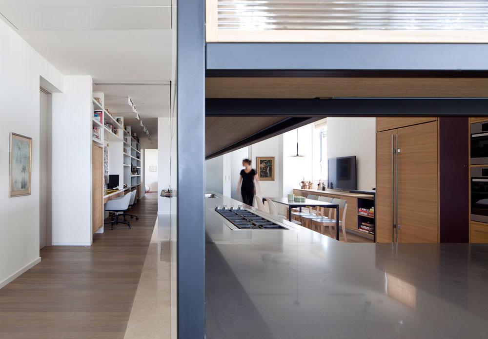 הפתחים שתוכננו בארונות מאפשרים לראות חלקים נרחבים מהדירה ותורמים לתחושת המרחב. לאורך ''שביל'' הפרקט שמוביל לחדר השינה נבנתה ספרייה  (צילום: עמית גרון)