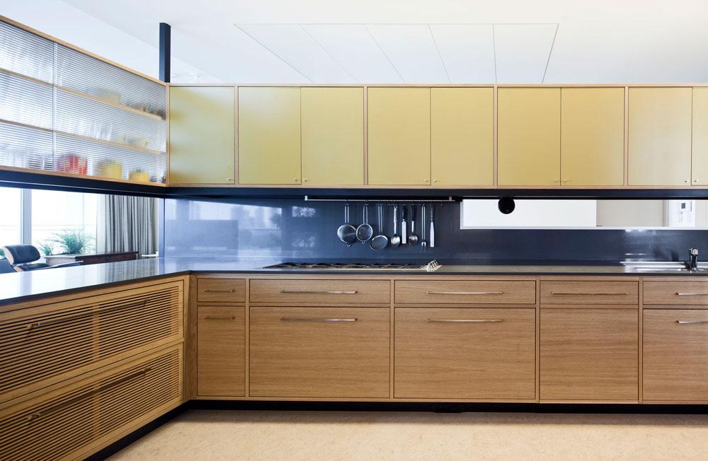 עיצוב המטבח שואב השראה מציוריו של מונדריאן, אומרים האדריכלים - שחור ועץ עם דלתות זכוכית ודלתות פורמייקה בצהוב-חרדל וסגול. משטח העבודה עמוק במיוחד. חלון מוארך בין הארונות התחתונים לעליונים מאפשר לעומדים במטבח לראות את הנכנסים לבית (צילום: עמית גרון)