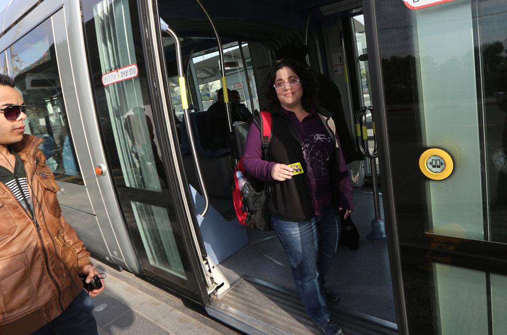 אורית עולה לרכבת הקלה בירושלים. לדבריה, הילדות נהנות מאוד מנסיעה ברכבת ובאוטובוס. ''ילד שרק מסיעים אותו הופך לעצלן'' (צילום: גיל יוחנן)