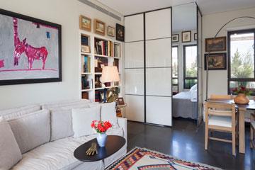 מחיצות זכוכית לבנה מפרידות בין הסלון לחדר האורחים  (צילום: שי אפשטיין)