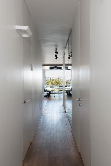 מסדרון לבן, שלאורכו דלתות החדרים וארונות אחסון (צילום: גדעון לוין)