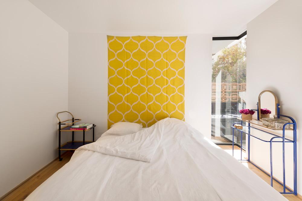 חדר ההורים עוצב מחומרים פשוטים: בגבה של מיטה בסיסית נתלה שטיח צהוב של ''איקאה'', מצדה האחד קונסולה ממתכת תכולה ובצד השני עגלת תה שמשמשת כשידת צד – שתיהן מחנות וינטג'. הפריטים ממוסגרים היטב בחלון פינתי גדול שפונה אל המרפסת, ובעזרת ארון עץ יפהפה עם ידיות עגולות גדולות (תמונה שלו תוכלו לראות בהמשך הכתבה) (צילום: גדעון לוין)