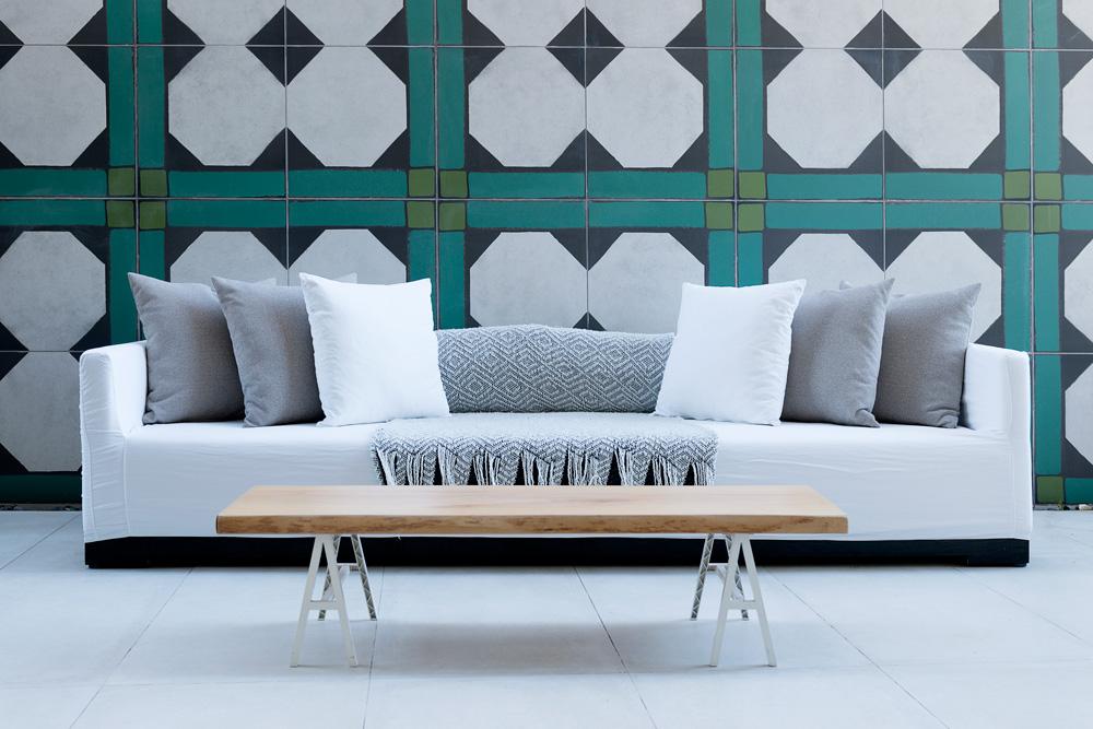 במרפסת יש ספה ארוכה, נשענת אל קיר שחופה באריחים גדולים ומאוירים כבמשיכות מכחול (צילום: גדעון לוין)