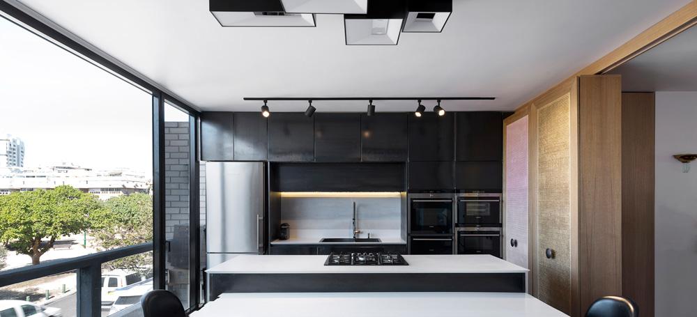 שלושת חלקי המחיצה הניידת משמשים מצד המטבח כארונות נוספים, צרים, עם דלתות מרשת קש בשלושה גוני פסטל שונים (צילום: גדעון לוין)