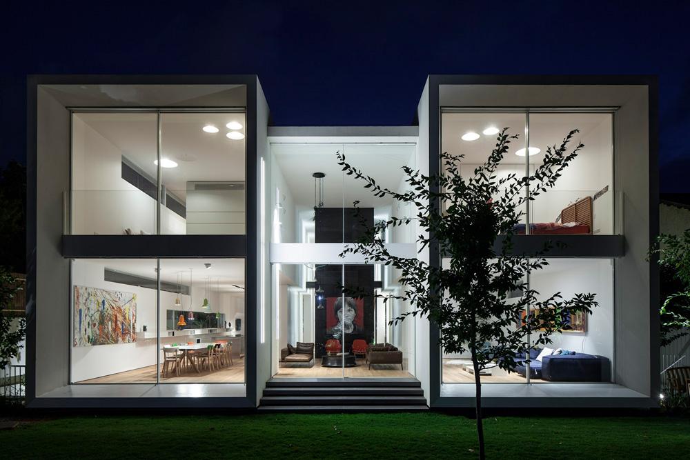 חזית שקופה ובצדדים קירות אטומים כמעט. בתמונה זו נראית היטב חלוקת הבית, עם החלל המרכזי, שמתנשא לגובה שתי הקומות (צילום: עמית גרון)