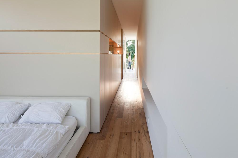 אגף ההורים: מבט מחדר השינה אל הקצה השני של הקומה, שם נמצא חדר הרחצה. באמצע חדר ארונות עצום, ומולו, מימין, הפתח שמוביל לגרם המדרגות (צילום: עמית גרון)