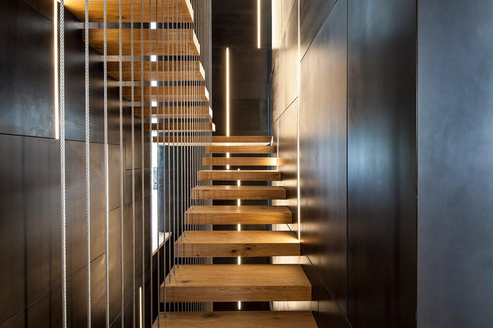 גרם המדרגות מבפנים. לוחות כהים מקיפים מדרכי עץ שתלויים על כבלים מתקרת הבית - פתרון שחוסך במעקות ובפרטי חיבור נוספים. פסי האור מדגישים את אורכיותו של הפיר (צילום: עמית גרון)