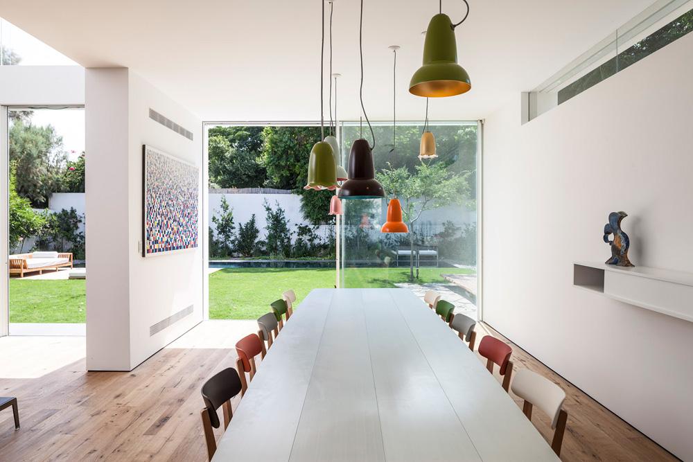 חלונות סרט צרים נפערו באקראי (כביכול) בקירות שפונים לבתי השכנים. בצד שפונה לגינה האחורית הקירות שקופים לגמרי. מבט מכיוון המטבח (צילום: עמית גרון)