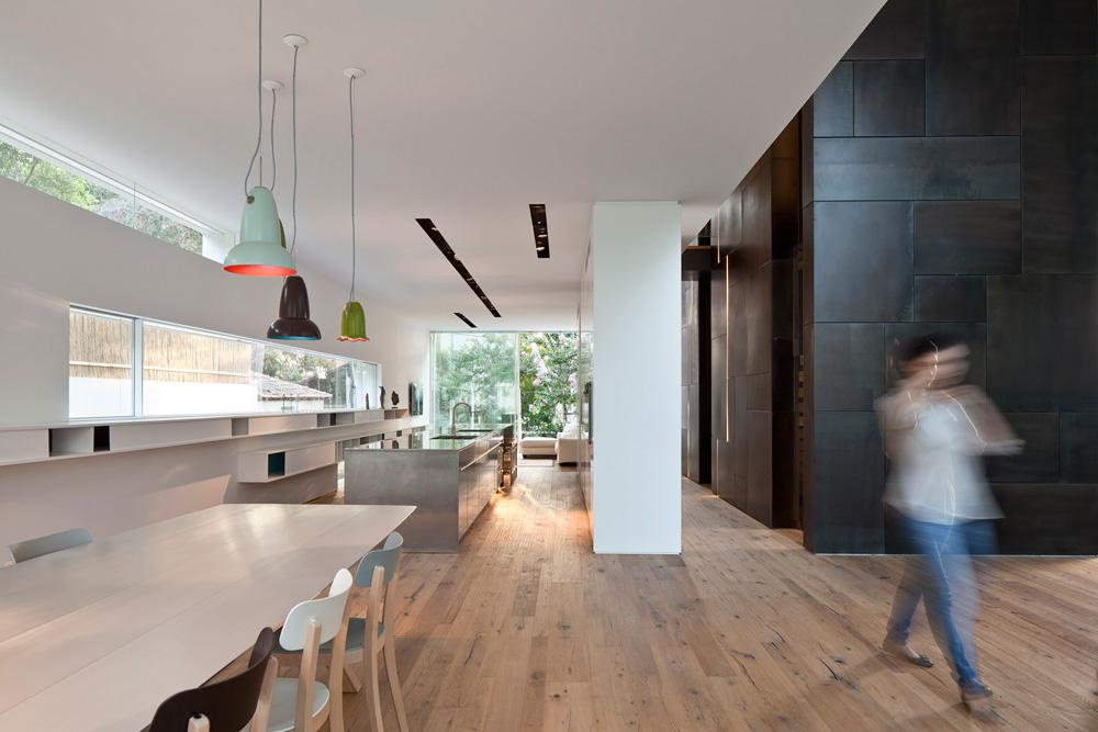 גם המטבח תוכנן בקווים מקבילים: במרכז אי באורך של 7 מטרים מנירוסטה, בצד אחד קיר ארונות לבנים ועל הקיר שמולו מדפים תלויים וארוכים, שנמשכים לתוך פינת האוכל (צילום: עמית גרון)