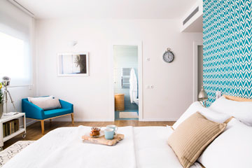 חדר השינה בדירה שתוכניתה מופיעה למעלה. כך נראות דלתות חדרי הרחצה והארונות מכיוון המיטה. עיצוב: אלה צייחר (צילום: איתי בנית)