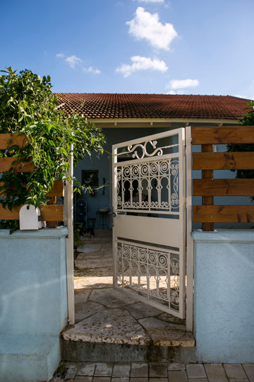 הבית מבחוץ. שער לבן וחזית צבועה תכלת (צילום: שירן כרמל)