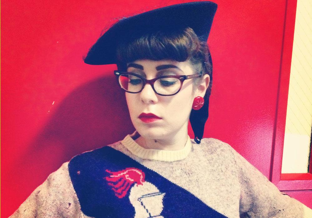 האנה לבושה במראה שנות ה-40 כמו תמיד, אבל עם טוויסט של ימי הביניים. את הסטיילינג היא יצרה לעצמה בהשראת השנים שבהן עבדה כספרנית, על הרקע של דלת החירום האדומה בבניין האוניברסיטה