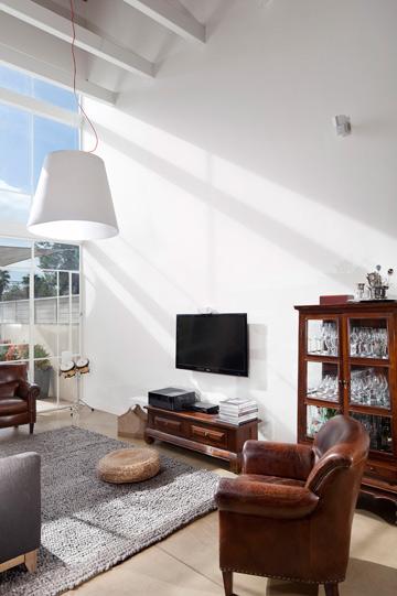 חלון שגובהו 6 מטרים מכניס את החצר והשמש פנימה. צלון רשת חשמלי מסנן את הקרניים (צילום: שי אפשטיין)