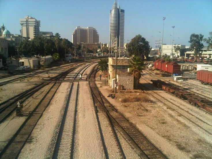 ומגדל קרית הממשלה בחיפה, הידוע בכינויו ''הטיל'', על רקע הרכבת המתחשמלת בקרוב