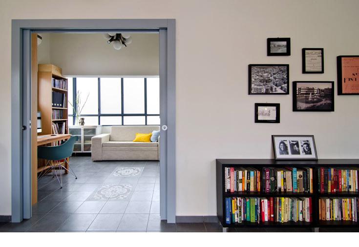מבט מתוך הסלון אל חדר העבודה/אורחים. על הקיר תמונות מרחובות השכונה בימיה הראשונים. על ספת האורחים כרית צהובה מאירה (צילום: אילן נחום )