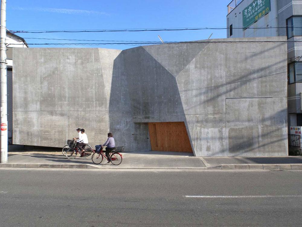 הניכור מתחיל מבחוץ: קירות שמסתירים את הבית ומונעים ממנו אור כמעט לחלוטין, ומזכירים כניסה למוסד מאובטח (צילום: SUGA ATELIER)