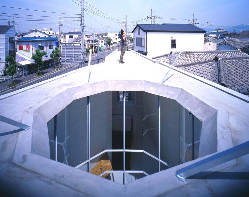 אור השמש חודר לבית המגורים הזה מלמעלה, באמצעות ארובת-אור שמחדירה אותו לכל הקומות - יחד עם מי הגשם שזורמים ללא הפרעה אל הבריכה בקומה התחתונה (צילום: SUGA ATELIER)