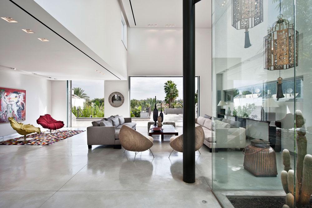 קומת הכניסה נראית גבוהה, בגלל השיפוע של המגרש הצר: הסלון יוצא אל מרפסת גדולה, שמשקיפה על הגינה והבריכה שמאחור, במפלס נמוך יותר. פטיו מוקף חלונות זכוכית ''מפצה'' על היעדר גינה מצדי הבית (צילום: עודד סמדר)