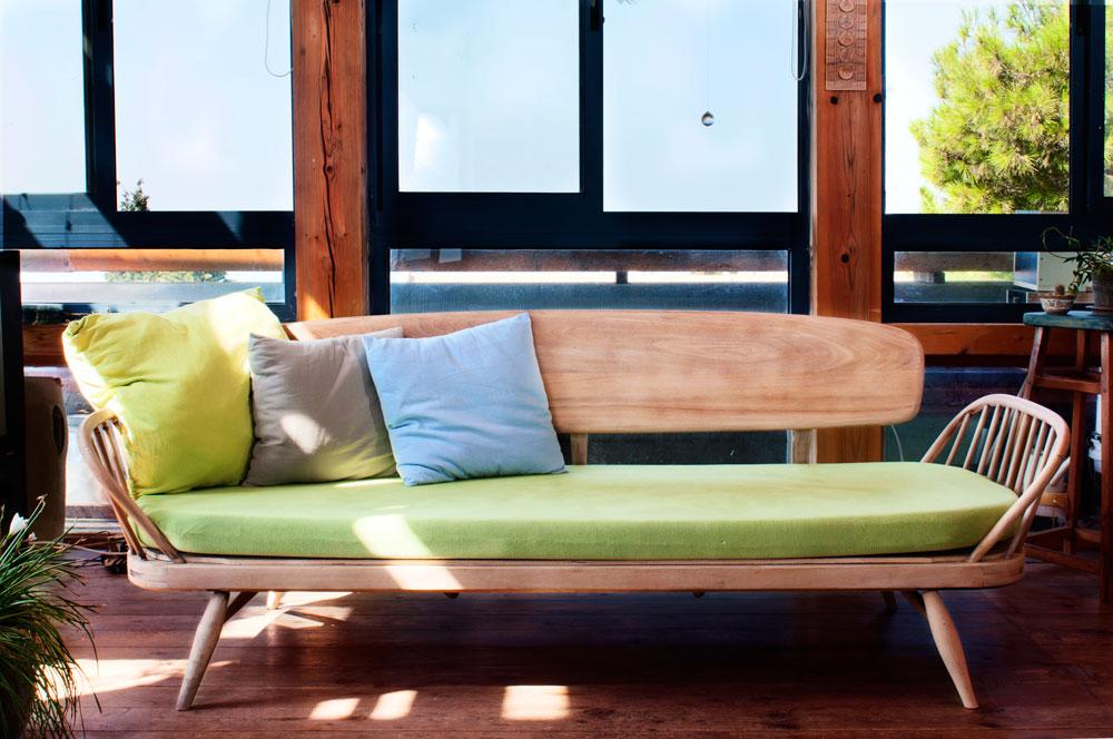 את הספה ראו בשוק הפשפשים אך נרתעו מהמחיר. לאחר שבועיים מצאו במקרה את תאומתה ברחוב, שיפצו אותה, חשפו את העץ ותפרו לה כריות חדשות (צילום: דורון עובד)