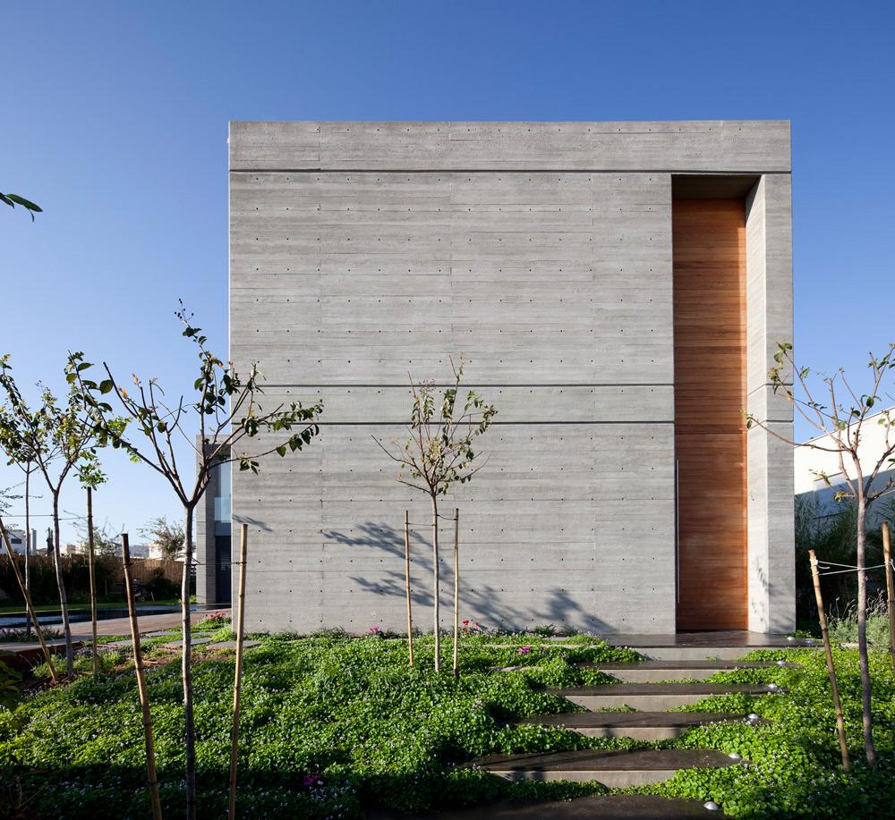 המקום: קיסריה. מטראז': 350 מ''ר על מגרש של 750 מ''ר. תכנון: אדריכל יואב אנדרמן. החזית הפונה לרחוב כמעט אטומה. דלת כניסה מעץ טיק ''שוברת'' את מסת הבטון (צילום: עמית גרון)