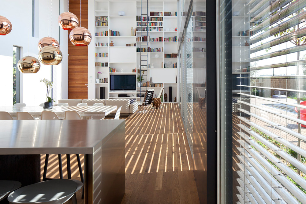 מבט אל הקיר שלכל גובהו נמתחות דלת הכניסה והספרייה. המנורות הכדוריות מעל שולחן האוכל בעיצוב טום דיקסון (צילום: עמית גרון)