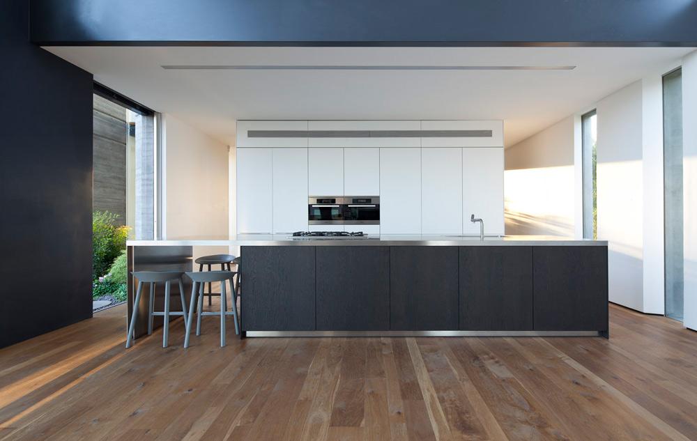 המטבח (''בולטהאופ'')) מורכב מקיר ארונות לבנים ו''אי'' מפורניר וונגה שעליו משטח נירוסטה. גובה החלל כאן משתנה: את המטבח מגדירה הקומה השנייה, ומעליו מוקמו שני חדרי הילדים  (צילום: עמית גרון)