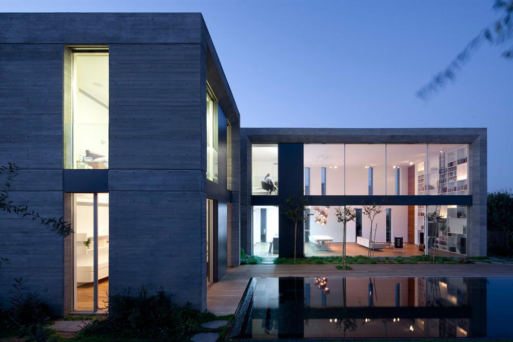 גובה חלל הסלון 6.15 מטרים. מצד אחד חלונות גדולים, הפונים לבריכה ולגינה. בצד השני, הפונה לבתים השכנים, חלונות צרים וארוכים, לטובת הפרטיות. קורות מודגשות וחיפויי פח יוצרים צלבים א-סימטריים בחזיתות השקופות, ומסגרת החלונות בולטת וקטומה, כדי להצל מעט על הבית (צילום: עמית גרון)