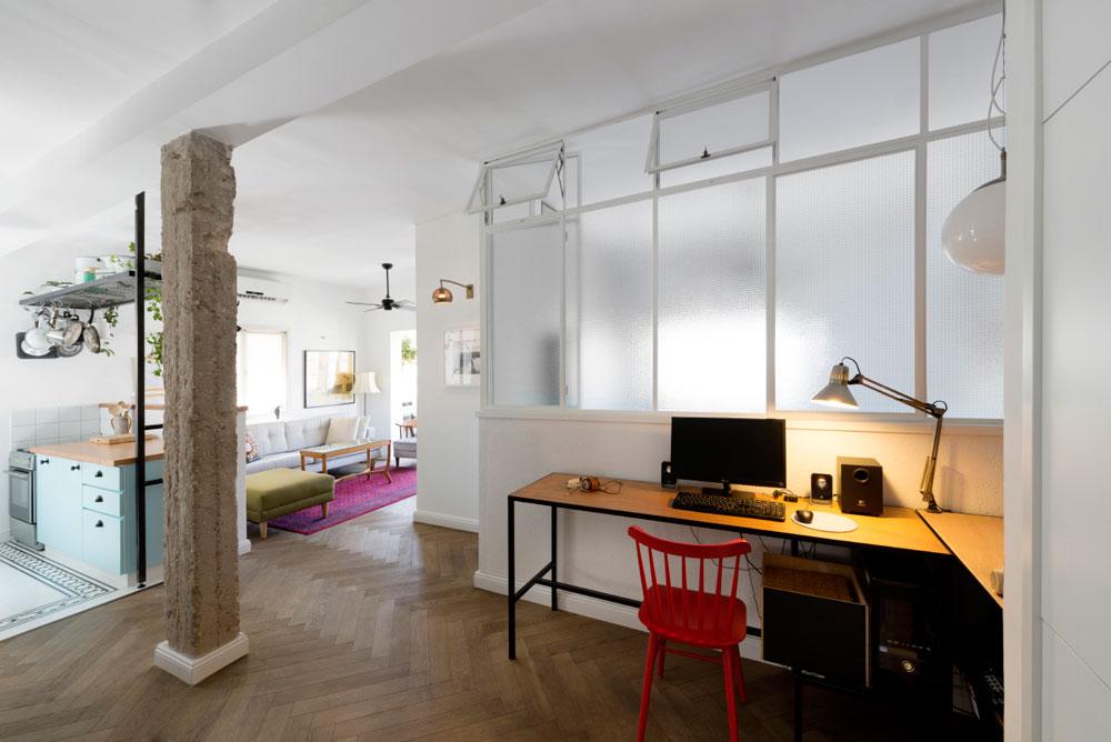 אזור המבואה והעבודה. קיר חדר השינה ''נדחף'' פנימה לטובת מרחב נוח לפינת העבודה, ורובו הורכב מזכוכית סבתא ממוסגרת בפרופילי ברזל, כדי להעביר אור מחדר השינה (צילום: גדעון לוין,181 מעלות )