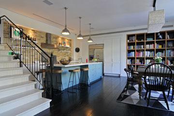 המטבח: קיר אחד של לבנים, קיר של ארונות לבנים, וספריית עץ אלון מעושן (צילום: שי אדם)