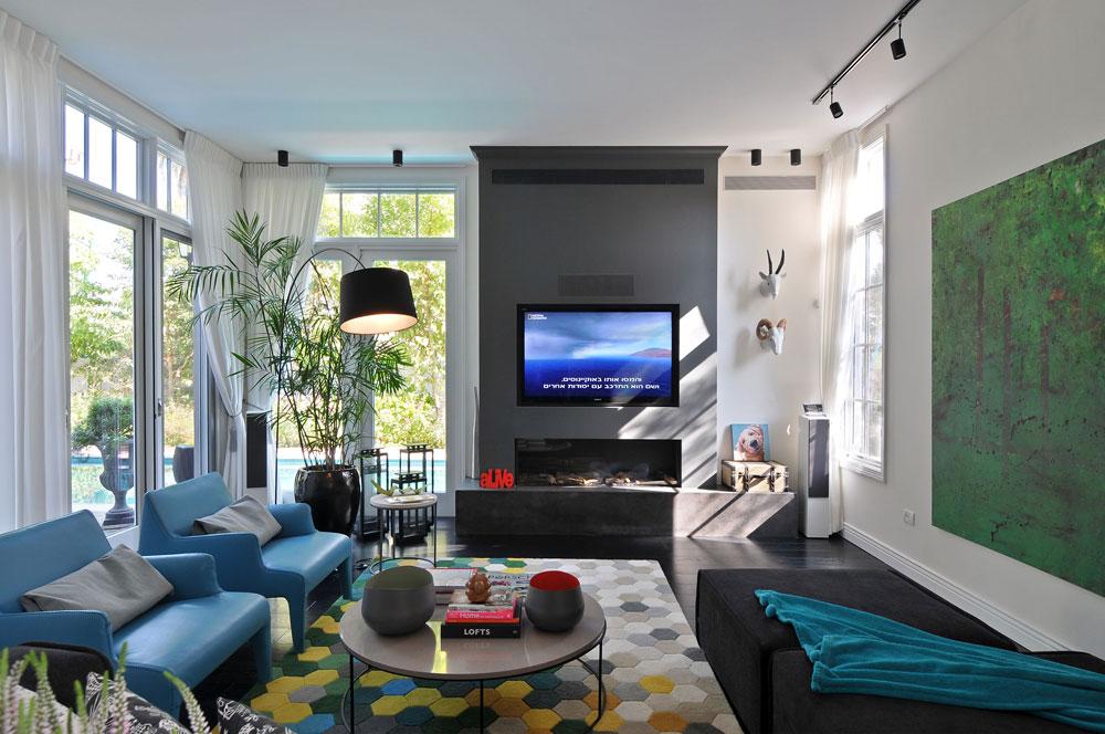 הסלון עוצב סביב קיר מרכזי באפור כהה, שבו קמין, טלוויזיה ומזגן. רצפת כל הבית חופתה בפרקט עץ שחור, והצבעים חמים ועוטפים, בסגנון האהוב על בעלת הבית (צילום: שי אדם)