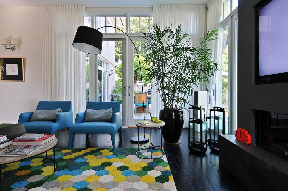כמו רוב החללים בקומה, הסלון פונה אל הגינה והבריכה. חלונות גדולים מפרידים בין הפנים לחוץ, ולגובהם נתלו וילונות בהירים, נשפכים (צילום: שי אדם)