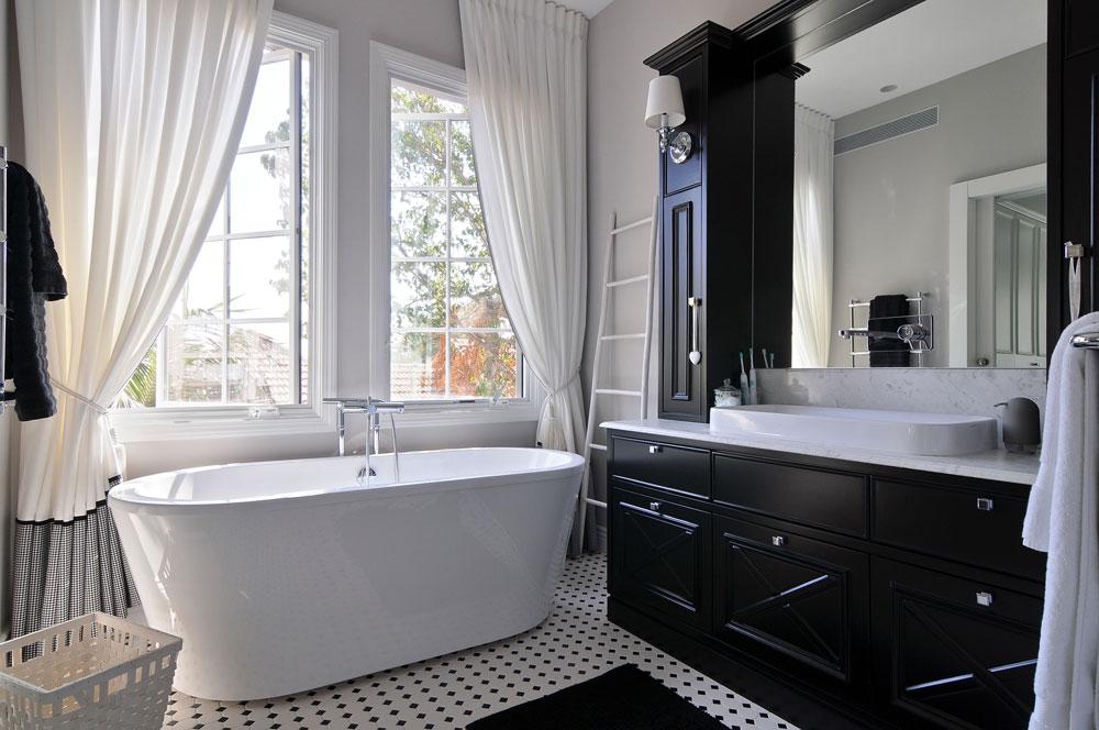 חדר הרחצה של ההורים בשחור ולבן. האמבטיה הוצבה מול החלון הגדול, וגם כאן הווילונות ארוכים ובעלי נוכחות (צילום: שי אדם)