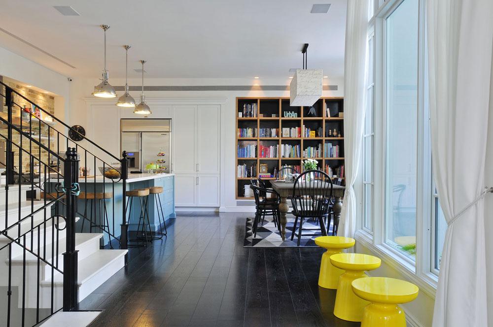 גרם המדרגות חוצה את הקומה לשניים. מולו חלון גדול, מודגש באמצעות שלושה שרפרפים צהובים, ומעברו השני המטבח ופינת האוכל (צילום: שי אדם)