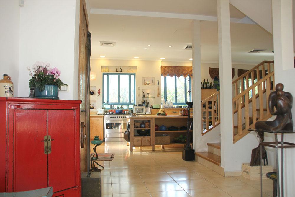 משמאל לדלת הכניסה המטבח, מימין הסלון, ומולה המדרגות לחדר השינה של בני הזוג. חוץ מהפסלים בולטים בבית פריטים בסגנון סיני, שבלוך ובן זוגה הביאו מניו יורק (צילום: מלכה שמיר)