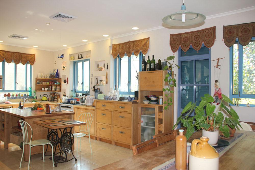 המטבח מעוטר בעבודות קרמיקה של בלוך. ל''אי'' במרכז צמוד שולחן לארוחות היומיום - פלטת עץ על רגליים של מכונת תפירה מסוג ''זינגר'', שהייתה של סבתה (צילום: מלכה שמיר)