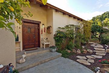 שביל אבנים המוביל לגינה חלומית ודלת עץ מרשימה מקדמים את פני הבאים (צילום: אבישי פינקלשטיין)