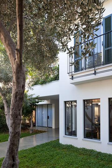 צבעי הבית: קירות לבנים, תריסים ירוקים כהים ופרופילי ברזל שחור (צילום: עמית גרון)