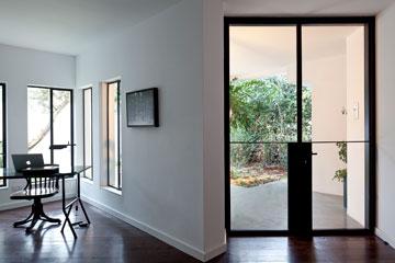 דלת הכניסה, מפנים. פרקט כהה, קירות לבנים וחלונות גדולים (צילום: עמית גרון)