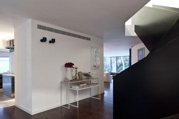 המטבח משמאל לדלת הכניסה. המרחב שבין הקיר לגרם המדרגות משמש כמבואת כניסה (צילום: עמית גרון)