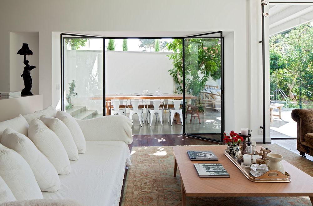 דרך החלון נשקפת פינת אוכל חיצונית – שולחן עץ וכסאות לבנים, תחת פרגולת עץ לבנה (צילום: עמית גרון)